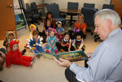 President Michael Alexander reads to visitors for Halloween